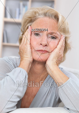 Senior Woman with Head In Hands Looking Worried Stock Photo