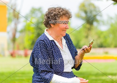 Senior Woman Checking Her Wrinkle With Mirror Outdoors Stock Photo