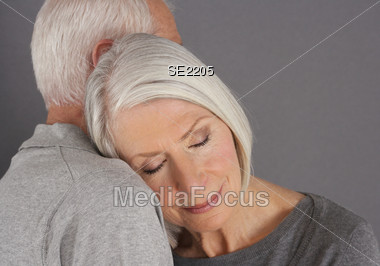 Senior Woman Resting Her Head on Man's Shoulder Stock Photo