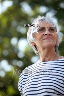 Senior Woman Walking In The Park Stock Photo