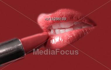 Sensual Pretty Woman Applying Cosmetics On Her Lips Close-up Shot On Purple Stock Photo
