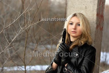 Sensual Young Woman Holding A Weapon In Front Of The Winter Forest Stock Photo