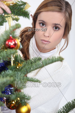 Serious Woman Placing An Ornament On A Christmas Tree Stock Photo