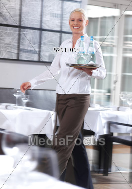 Server Carries Tray Of Drinks Through Restaurant Stock Photo
