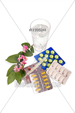Set Of Tablets And Capsules With A Thermometer, The Water In A Crystal Glass And A Branch With Pink Flowers And Green Leaves Stock Photo