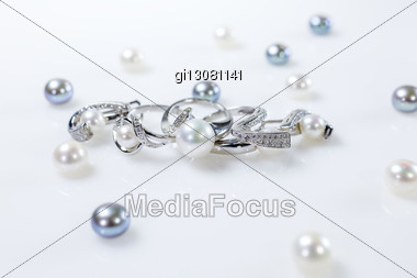 Set Of Two Rings And Earrings With Pearls. Objects Lying On A White Table Surrounded By Pearls Of Different Colors Stock Photo