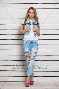 Sexy Blond Woman Posing In Blue Jeans Near White Wooden Wall Stock Photo