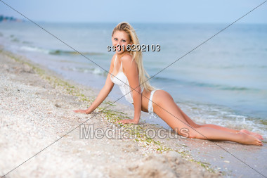 Sexy Blond Woman In White Lingerie Lying On The Beach Stock Photo