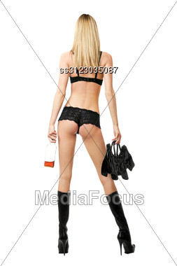 Sexy Blonde With Handbag And Bottle In Her Hands. Rear View Stock Photo