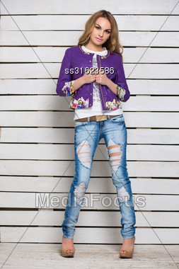 Sexy Blonde In Ripped Jeans And Purple Jacket Posing Near The White Wooden Wall Stock Photo