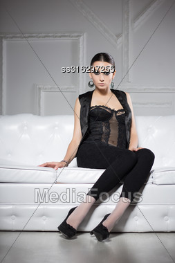 Sexy Brunette In Black Clothes Posing On White Sofa Stock Photo