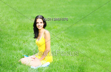 Sexy Brunette In Dress On The Background Of Green Grass Stock Photo