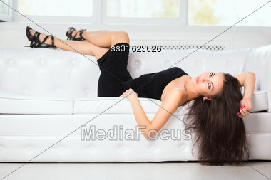Sexy Brunette Posing On A White Sofa In The Studio Stock Photo