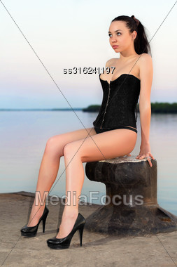 Sexy Brunette Wearing Black Corset, Panties And Shoes Posing On The Pier Stock Photo