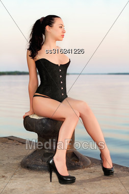 Sexy Brunette Wearing Black Corset Posing On The Pier Stock Photo