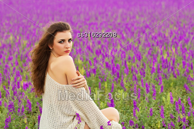 Sexy Curly Brunette Showing Her Bare Shoulder In A Flowering Field Stock Photo