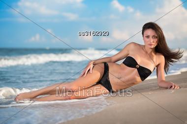 Sexy Slim Brunette In Black Bikini Posing On The Beach Stock Photo