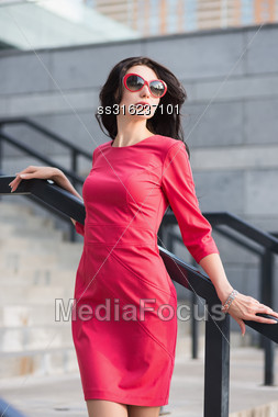 Sexy Slim Lady In Red Dress And Sunglasses Posing Near The Stairs Outdoors Stock Photo