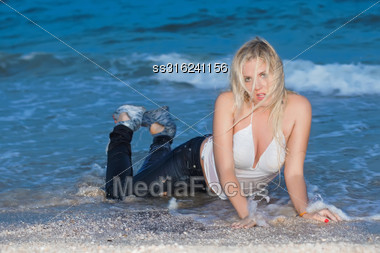 Sexy Young Blonde In Wet Clothes Posing On The Beach Stock Photo