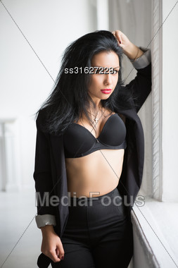 Sexy Young Brunette In Black Clothes Posing Near The Window Stock Photo