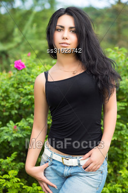Sexy Young Brunette In Black T-shirt Posing Near The Bushes Stock Photo