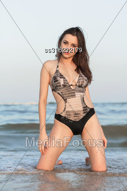 Sexy Young Brunette Posing On Her Knees In The Sea Stock Photo
