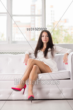 Sexy Young Brunette Posing On The White Couch Stock Photo