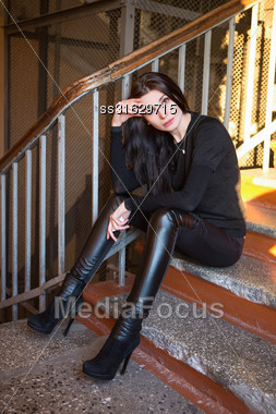 Sexy Young Brunette Wearing Fashionable Clothes Posing On The Stair Stock Photo