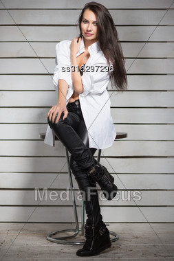 Sexy Young Brunette Wearing Fashionable Clothes Posing On The Chair Stock Photo