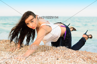 Sexy Young Brunette In Wet Clothes Posing On The Beach Stock Photo