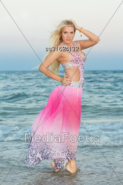 Sexy Young Woman In Pink Dress Posing On The Beach Stock Photo