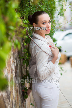Sexy Young Woman Wearing White Pants And Jacket Posing Near The Wall Stock Photo
