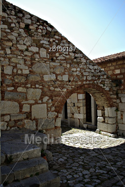 Shadow Detail Of Medieval Fortress, Stone Walls And Entrance Against Clear Blue Sky At Sunny Summer Day. Stock Photo