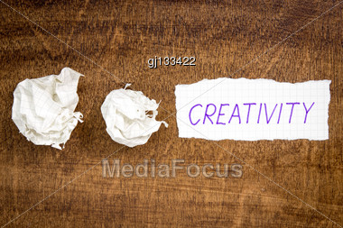 Sheet Of Paper With Word CREATIVITY And Crumpled Wads On Table Stock Photo