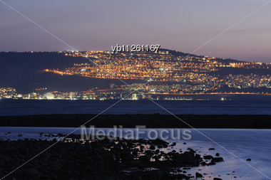 Shore Of Lake Kinneret And The City Of Tiberias At Night Stock Photo