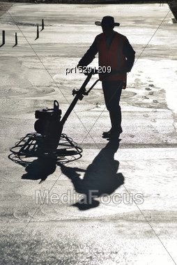 Silhouette Of Builder Floating Off Concrete Pad For A Large Building Stock Photo