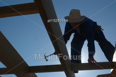 Silhouette Of A Builder Working On Flooring Of A Two-storey House Stock Photo