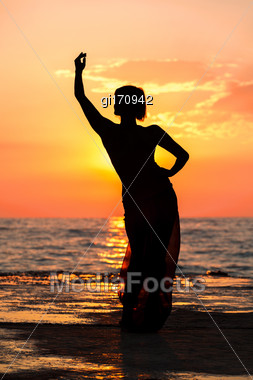 Silhouette Of A Girl Dancing On The Background Of Sea Sunset Stock Photo