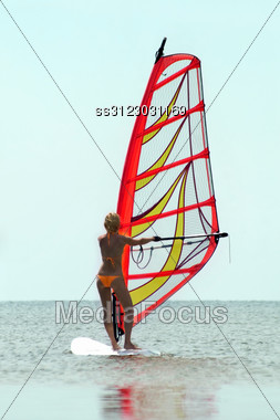 Silhouette Of A Girl Windsurfer On Sea Surface Stock Photo