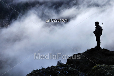 Silhouette Of A Hunter Scoping For Himalayan Tahr In The Southern Alps Of New Zealand Stock Photo