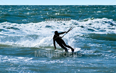 Silhouette Of A Kitesurfer On Waves Of A Sea Stock Photo