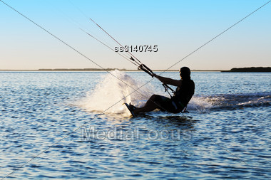 Silhouette Of A Kitesurfer Sailing In The Sea At Sunset Stock Photo