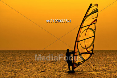 Silhouette Of A Windsurfer In The Evening Sea Stock Photo
