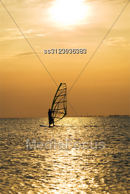 Silhouette Of A Windsurfer On A Sunset Stock Photo