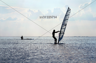 Silhouette Of A Windsurfer On The Water Surface Stock Photo