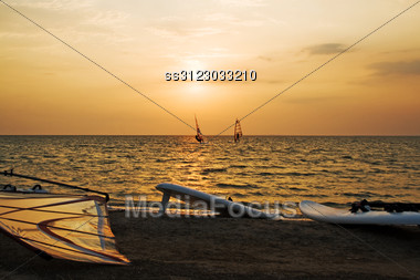 Silhouette Of A Two Windsurfer On A Gulf On A Sunset Stock Photo