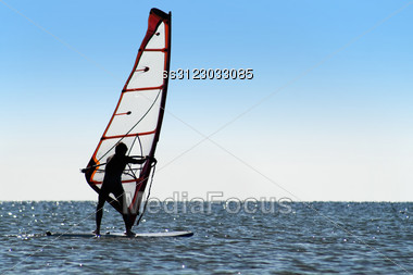 Silhouette Of A Windsurfer On The Blue Sea Surface Stock Photo