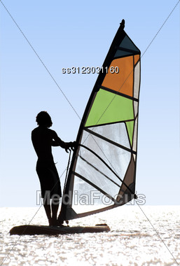 Silhouette Of A Windsurfer On Waves Of A Bay Stock Photo