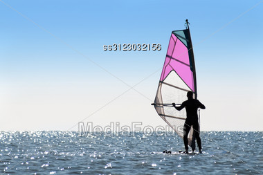 Silhouette Of A Woman Windsurfer On Sea Surface Stock Photo