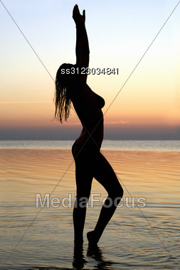 Silhouette Of A Young Woman Standing In Water Stock Photo